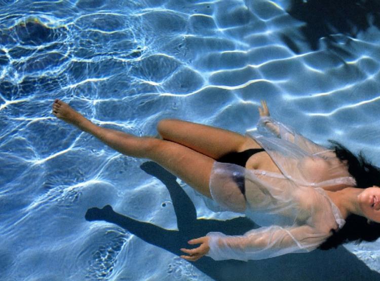 Эротично плавает в бассейне