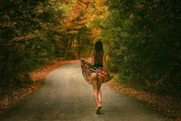 Девушка гуляет по осенней дороге