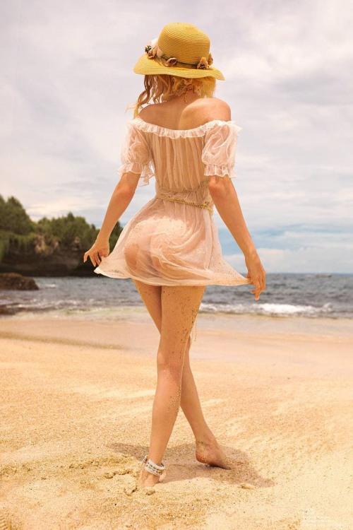 Девушка в прозрачном платье гуляет по пляжу